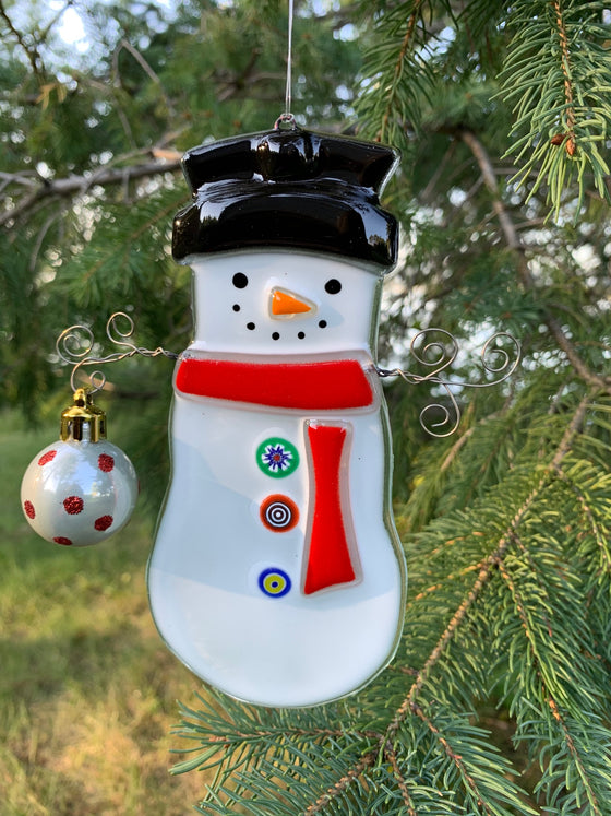 "A fused glass ornament depicting a snowman with a carrot nose and a ""coal smile"". It is wearing a top hat and a red scarf. Its arms are made of wire and one arm is holding a round ornament."