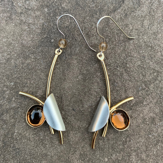 Polarizing pair of earrings in a bright gold finish with an amber stone set off to the side and a silver metallic piece folded over the opposite side.