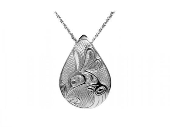 A silvery teardrop shaped pendant with a Haida design of a hummingbird drinking from a flower.