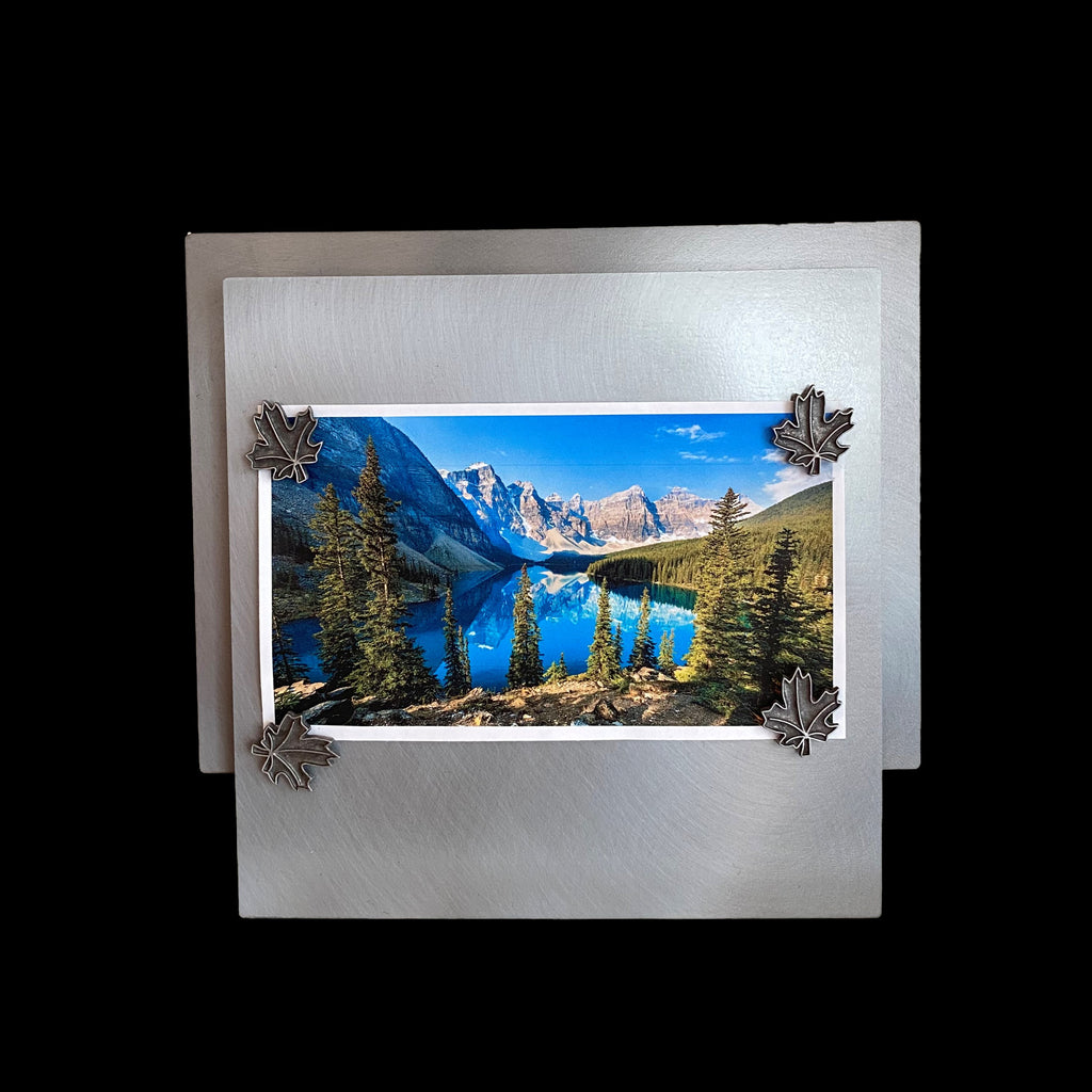 "This frame consists of a square, with a rectangle offset upwards and 1/4"" behind the square. A photo of a lake with mountains lining it on the left, and pine forest on the right is held on to the frame by four maple leaf shaped magnets."