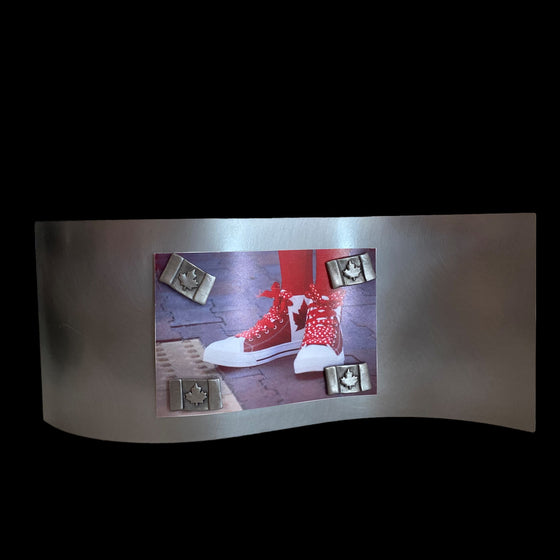 This frame consists of a single rectangular sheet of brushed steel, bent in a wave pattern so the single sheet stands on its own. A photo of someone's Canadian flag shoes is held on by four pewter magnets in the shape of Canadian flags.