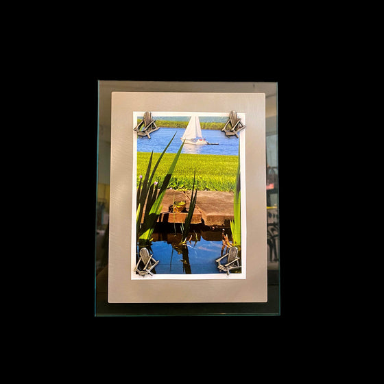 This frame consists of a rectangular sheet of brushed steel on a larger rectangle of glass. A photo of a grassy bank by a lake with a sail boat in the distance is held on by four pewter magnets in the shape of muskoka chairs.