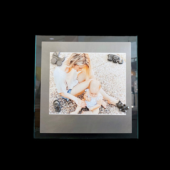 This frame consists of a square sheet of brushed steel on a larger square of glass. A photo of a woman sitting with her child is held on with the baby magnet set.