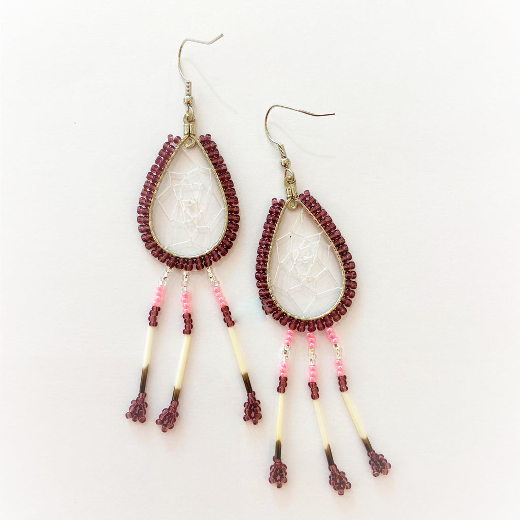 A pair of porcupine quill earrings. The hanging earrings are a tear drop shape hoop with dream catcher style weaving on the inside. Purple beads are woven along the outside of the hoop and hanging off of the bottom are three strands with silver, pink, and purple beads, then a piece of porcupine quill, with more purple beads at the end.