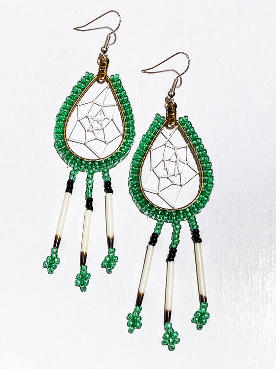 A pair of porcupine quill earrings. The hanging earrings are a tear drop shape hoop with dream catcher style weaving on the inside. Green beads are woven along the outside of the hoop and hanging off of the bottom are three strands with green and black beads, then a piece of porcupine quill, with more green beads at the end.