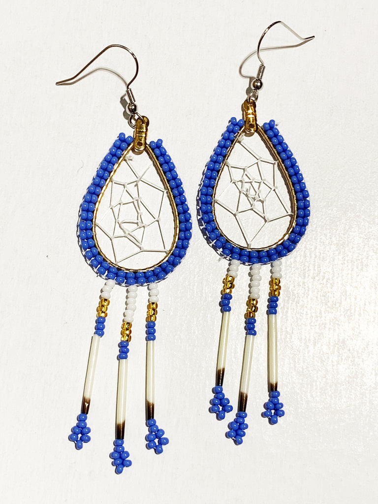 A pair of porcupine quill earrings. The hanging earrings are a tear drop shape hoop with dream catcher style weaving on the inside. Blue beads are woven along the outside of the hoop and hanging off of the bottom are three strands with white, gold, and blue beads, then a piece of porcupine quill, with more blue beads at the end.
