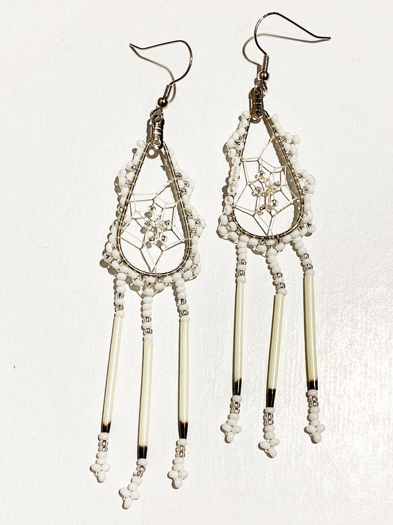A pair of porcupine quill earrings. The hanging earrings are a tear drop shape hoop with dream catcher style weaving on the inside with silver beads woven into it. White and silver beads are woven along the outside of the hoop and hanging off of the bottom are three strands with white and silver beads, then a piece of porcupine quill, with more white and silver beads beads at the end.