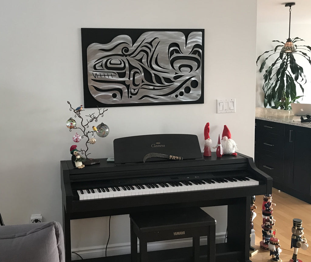 A Coastal Salish Orca wall sculpture hung on a wall. This brushed metal sculpture has been mounted on a black mounting board before being hung to provide contrast between the sculpture and the white wall behind it.