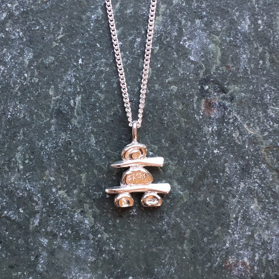 A handmade, sterling silver Inukshuk hanging from a fine silver chain.