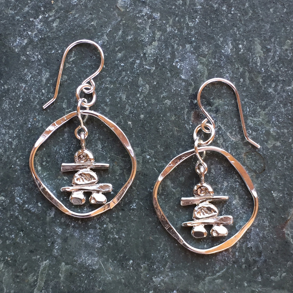Two sterling silver Inukshuk hook earrings. Each handmade Inukshuk is unique and shaped slightly different than each other. The Inukshuk are encircled by beaten silver hoops.