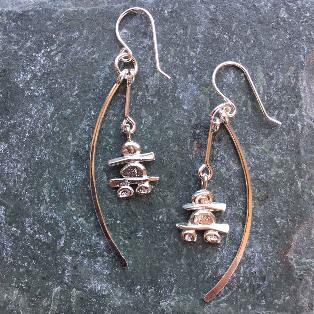 Two sterling silver hook earrings featuring an Inukshuk and a long shallow crescent. The Inukshuk hang down to the middle of the crescents. Each handmade Inukshuk is unique and shaped slightly different than each other.
