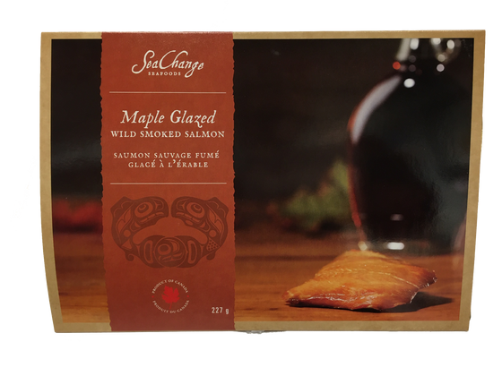 Picture features a single 227g portion of maple smoked salmon contained in a travel pack. On the travel pack, there is a small space alocated for haida art of the Canadian pacific salmon by artist Don Yeomans. However, the focal aesthetic feature of this product is an image of  an unwrapped portion of maple smoked salmon on a charcuterie board.