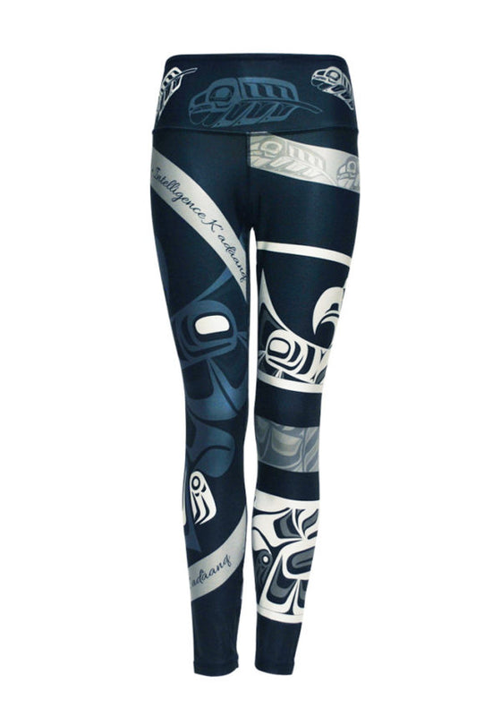 "These navy blue leggings are decorated with a motif of Haida eagles and eagle feathers, drawn in lighter blue, grey and white. A ring of feathers circles the waist. A white eagle with spread wings encircles the left leg, and another raven in light blue encircles the right. Also around the right leg are two grey stripes with the word ""intelligence"" written in English and Haida."
