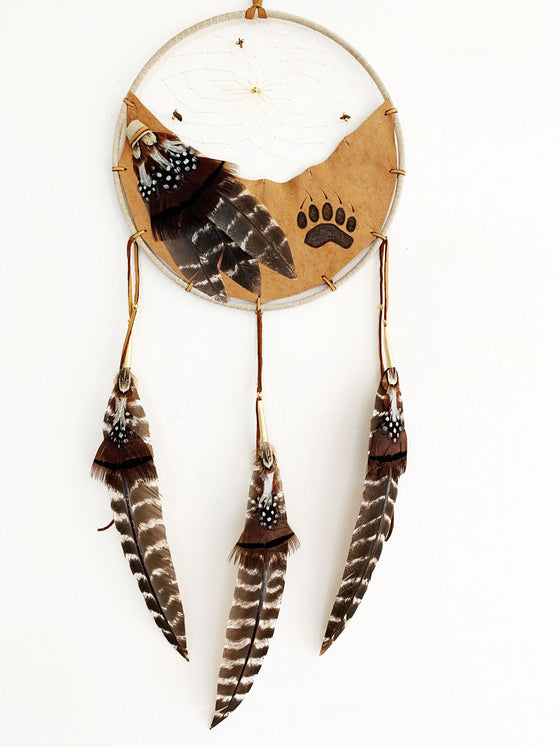 This dream catcher features a crescent of tan leather with a bear's paw print branded onto it. Above the leather, string is woven in a spiral pattern with small rocks and beads threaded into it. White, black and brown feathers lay across the leather on the left, and hang from three leather strings along the bottom.