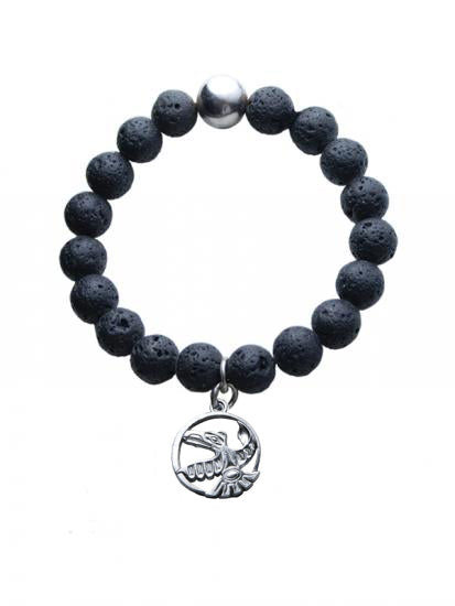 A bracelet made up of stringed lava beads, with one silver bead opposite to the raven charm. The charm is a special pewter-silver alloy and is an encircled Haida style raven in flight.