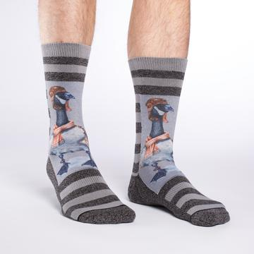 These fun socks feature a canada goose dressed in a leather aviator hat and scarf with a grey background behind him. Light and dark grey stripes fill the space above and below the goose, and the sole, toe, and heel are the same dark grey as the stripes. The active fit socks sport elastic arch bands to contour to your feet and provide support.