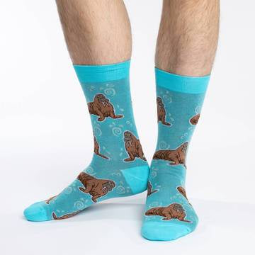 These fun socks feature large brown walruses sitting on a light blue background with while swirls and splashes, with a bright blue toe, heel, and rim. Spandex added to the 85% cotton blend gives the socks the perfect amount of stretch to hug your feet.