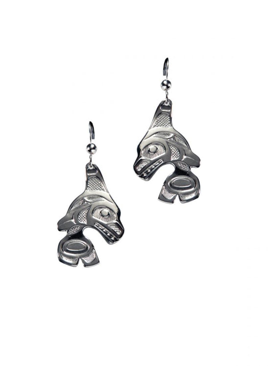 Two silvery earrings with Haida designs of orcas jumping.