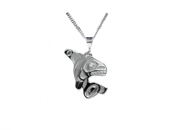 A silvery pendant with Haida designs of an orca jumping.