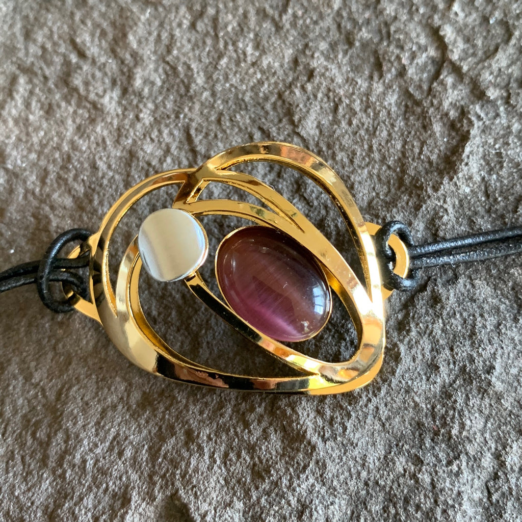Black leather bracelet with a mirror finish golden piece. The metal piece surrounds an oval of plum-coloured glass and a pearlesque circle piece