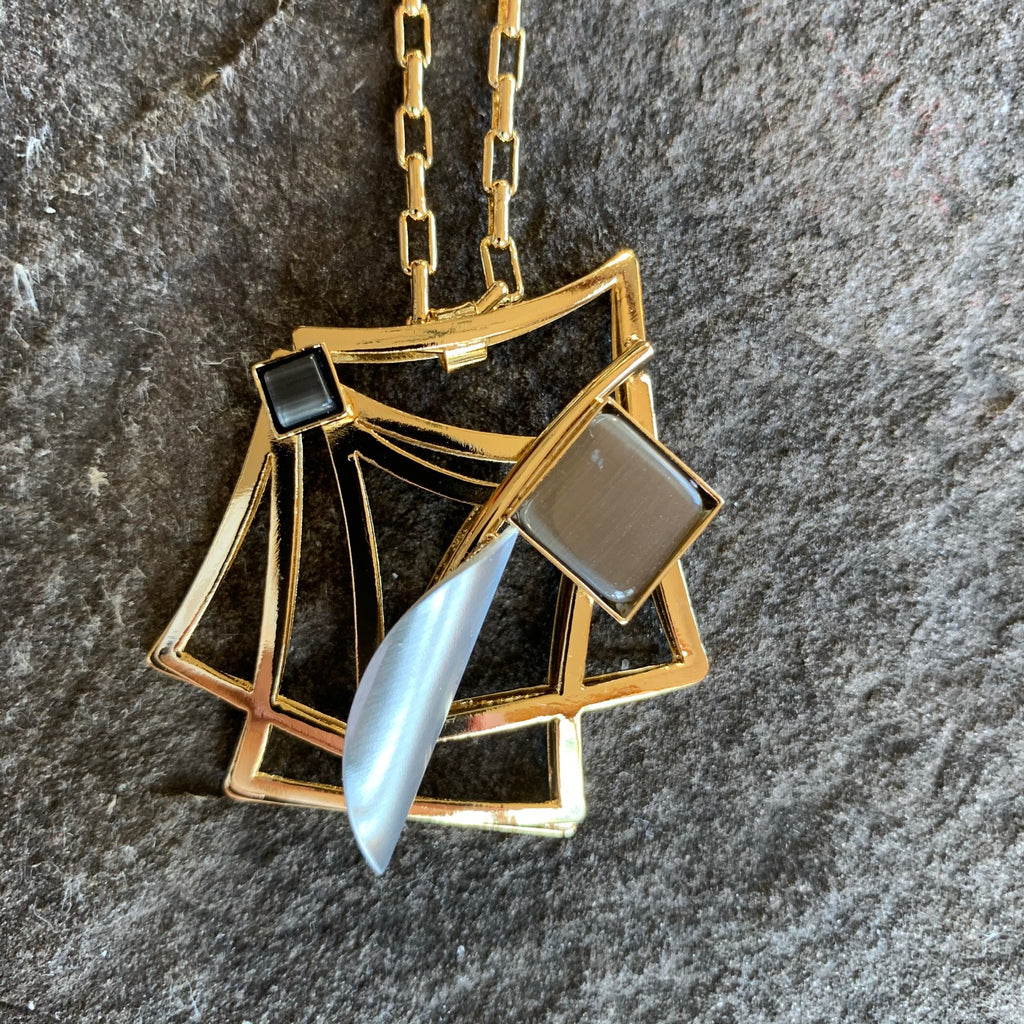 A very angular piece with bright gold squared surrounding silver and black pieces of glass to either side of the design.