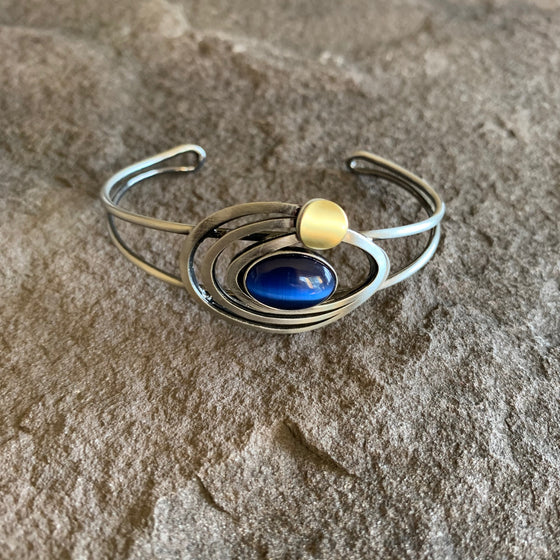 Silver cuffed bracelet with a main blue glass piece surrounded by swirls of silver and a brass circle offset from the main piece