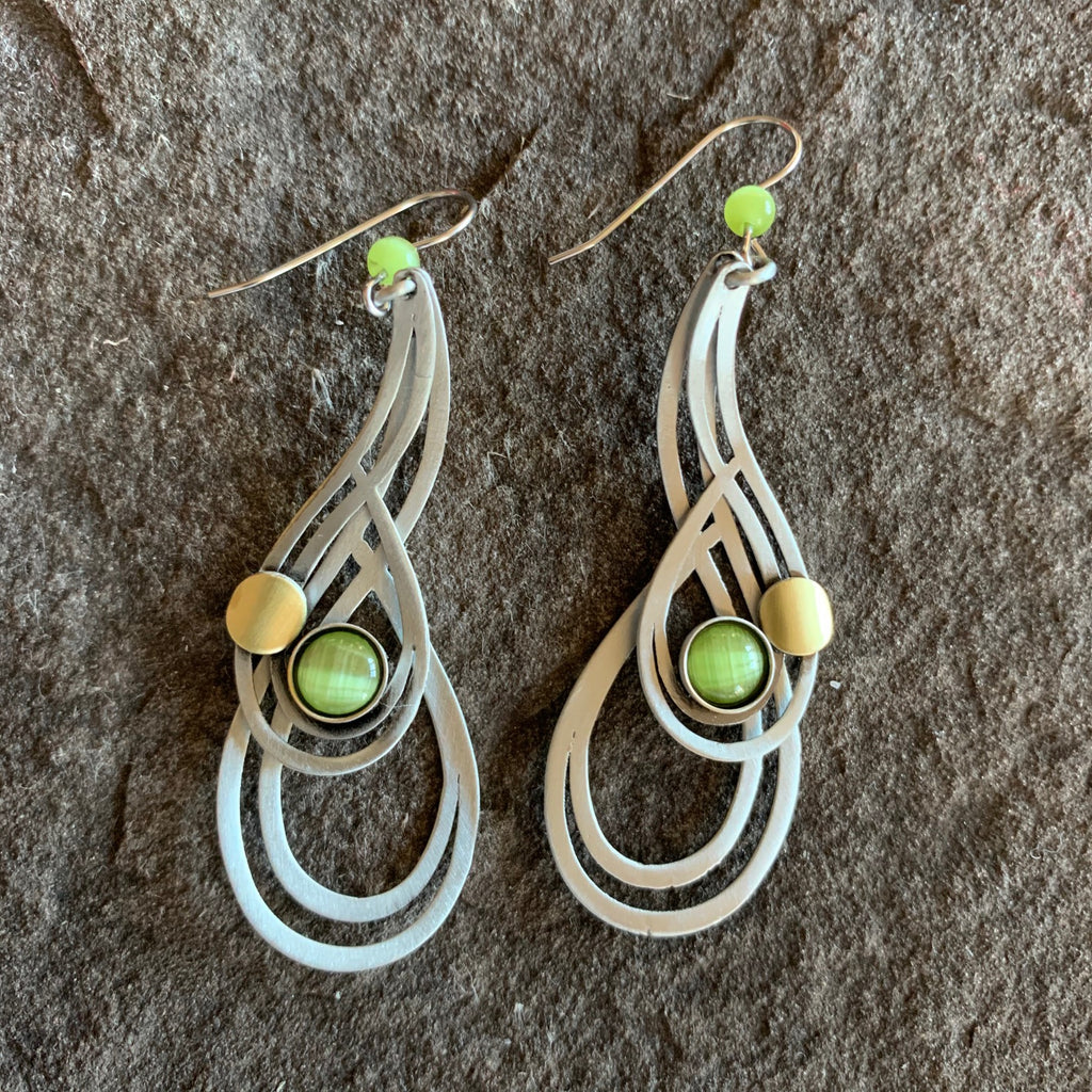 Drop bell shaped brushed silver metallic earrings with concentric bell shapes surrounding an olive gem in the middle accompanied by a brass circular piece.