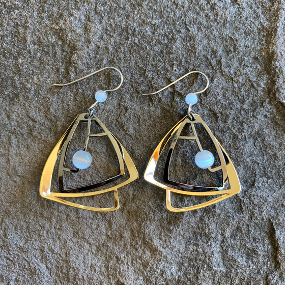 Sophisticated earring style with rounded pyramid shapes in bright gold finish, decorated with light grey or white circular beads and stones.