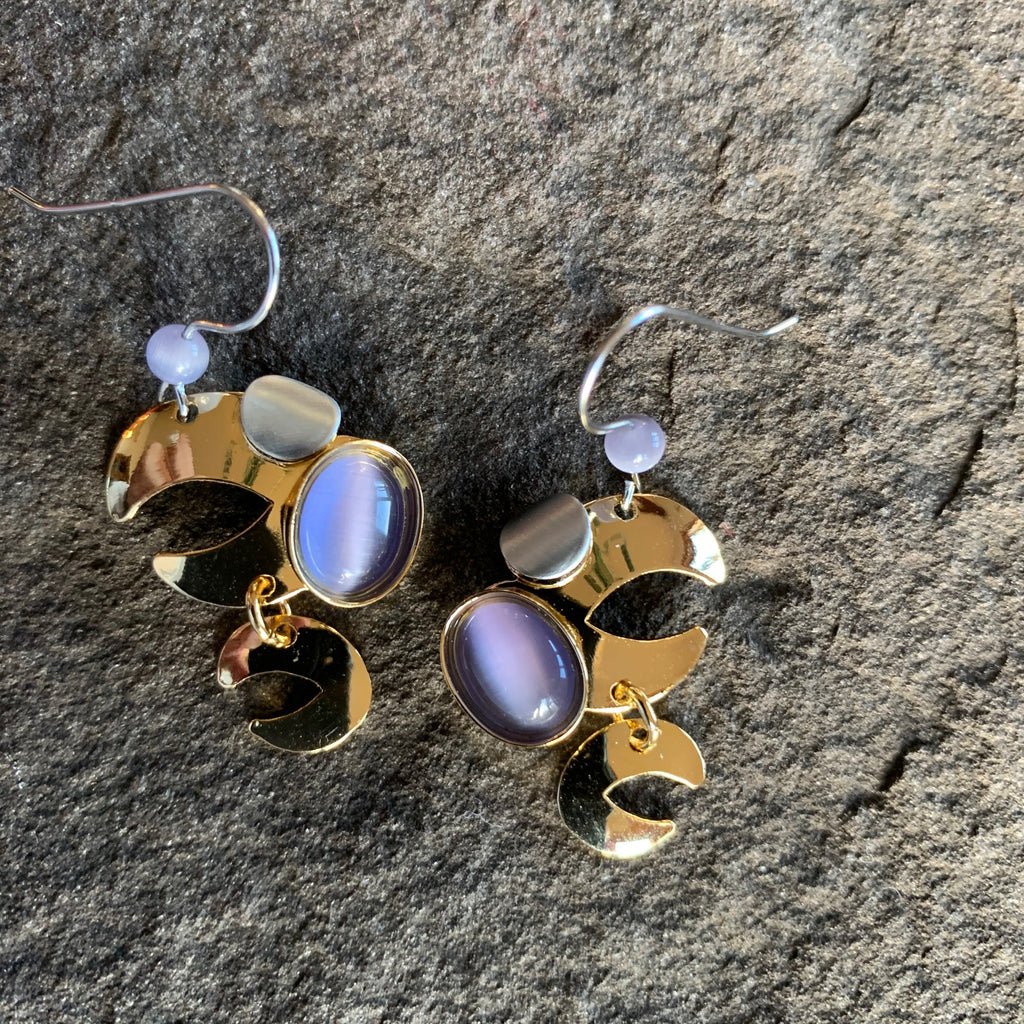 Very abstract style earrings in a bright gold finish with pirple accent stones surrounded by the golden C shapes that make up te design of these earrings.