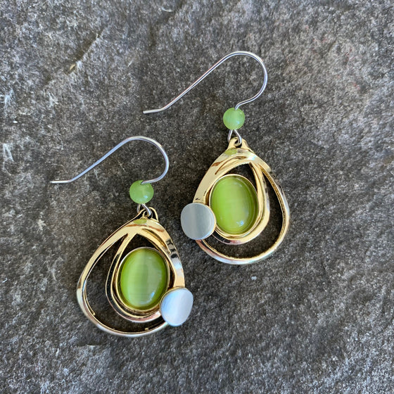 A bright gold pair of tear shaped earrings cradling a =n olive coloured green piece of glass, acompanied by a high brushed silver circle.