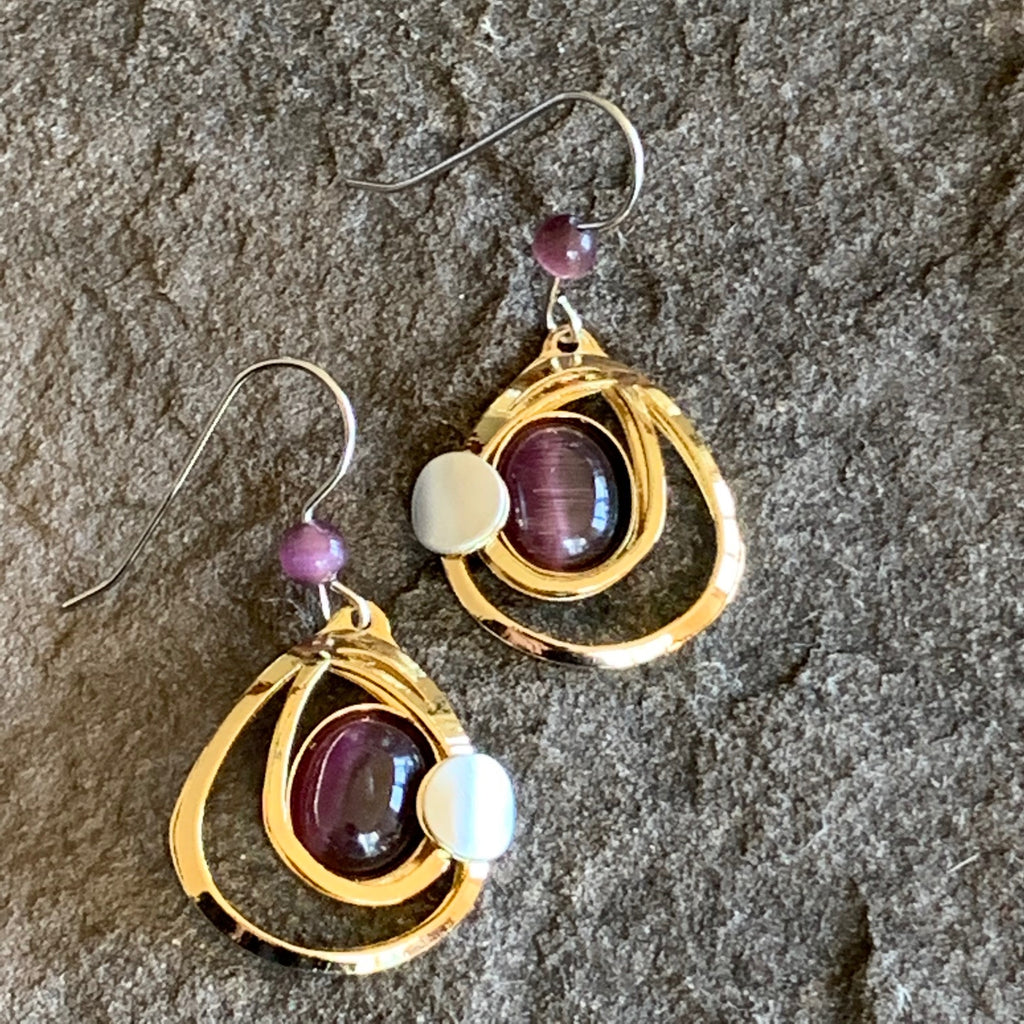 Circular bright gold earrings with two concentric rings surrounding a plum coloured centerpiece.