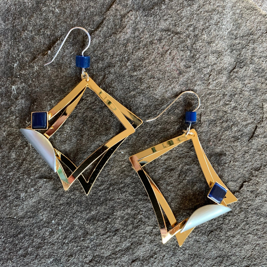 A pair of large hook earrings featuring two bright gold rectangles, a silver accent, and a square of clear blue glass