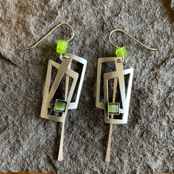 Very angular earrings, they are comprised of two interlocking brushed silver coloured metal rectangles ornamented with green glass and a bright green bead.