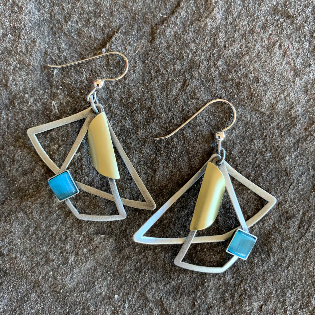 Angular earring design in a brushed silver finish. These earrings feature triangles overlapping quarilaterals and a focal piece in turquoise glass accompanied by a brass circle folded in an open half