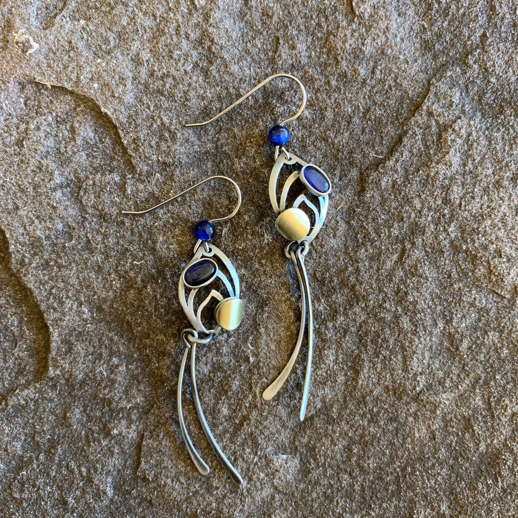 Beautiful whimsical looking earrings, made of a brushed silver metal, adorned with a deep blue stone and bead
