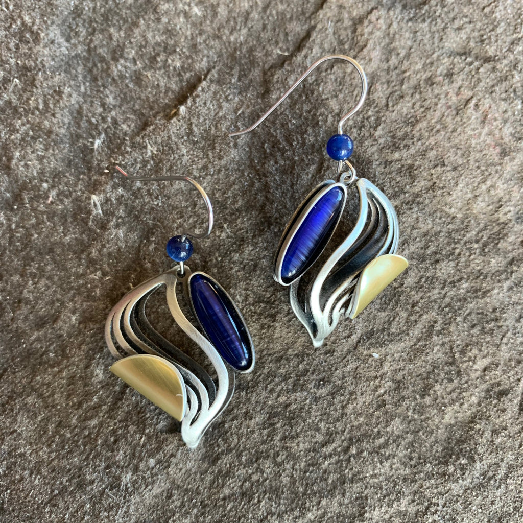 brushed silver finished earrings in the shape of a three-dimensional figure S, cradling a dep blue glass piece.