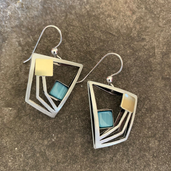 A pinched square shape earrings in a matte silver finish, this design has several offset squares within the larges one all leading in towards the focal piece of the earring which is a turquoise square.