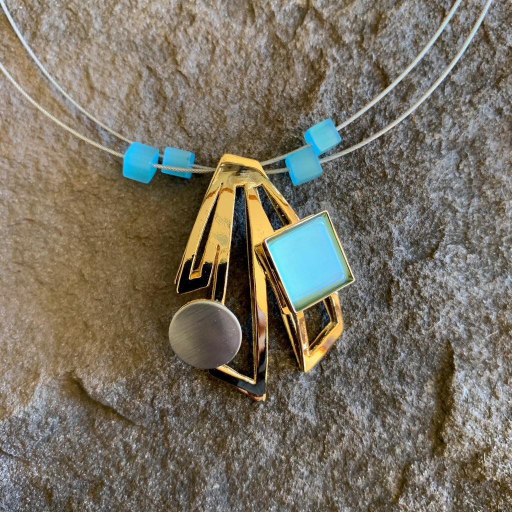 Bright gold coloured metal necklace with a square turquoise piece. The golden metallic part in offset rectangular.
