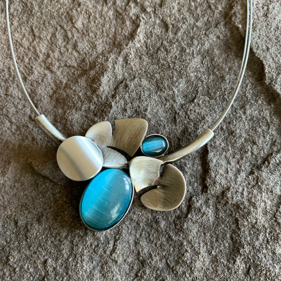 A brushed metal piece that is very reminiscent of a floral pattern, the metal pieces look somewhat like leaves. This piece is also adorned with turquoise glass ovals and a pearlesque circle.