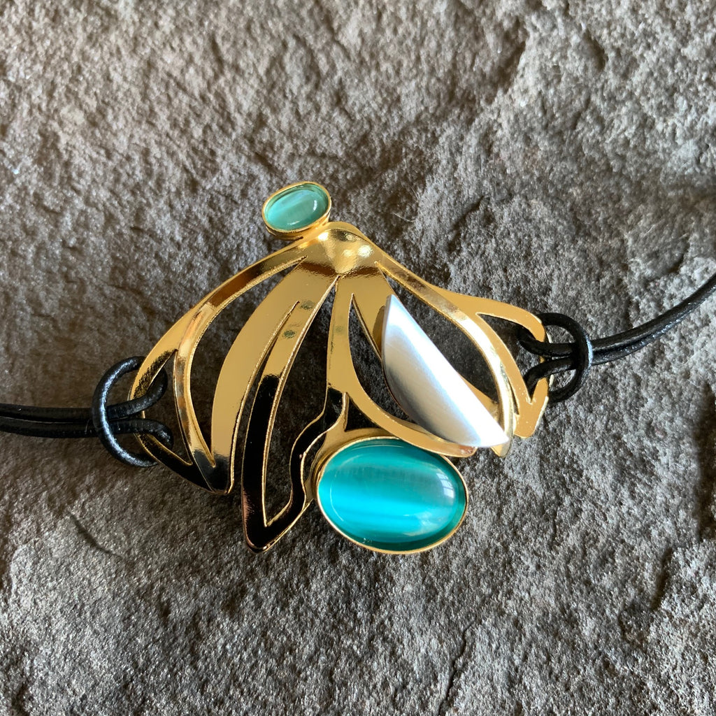 Black leather bracelet with a mirror finished golden metallic piece adorned with two turquoise glass pieces and a pearlesque accent piece. The metal piece resembles an amalgamation of semicircular and offset closed circular patters