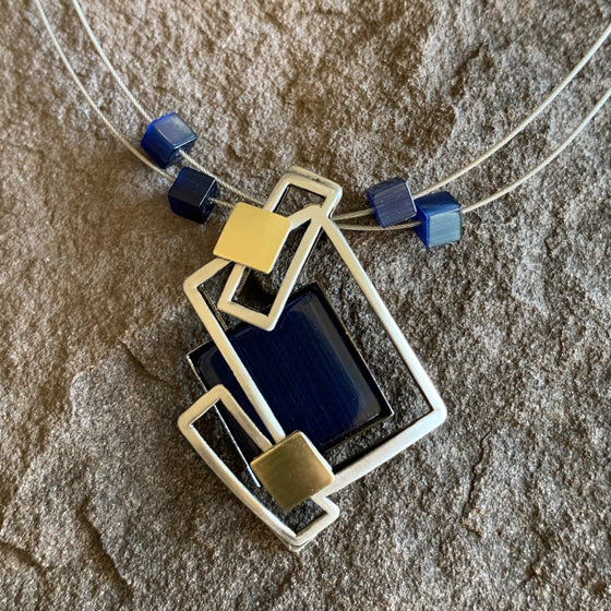Extremely angular necklace made of a brushed silver metal forming sharp rectangles and a large deep blue glass piece.