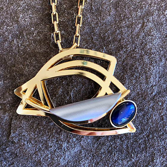 Bright gold piece with concentric rings swirling together to form the illusion of an empty eye. This piece includes a blue glass piece at the bottom corner.