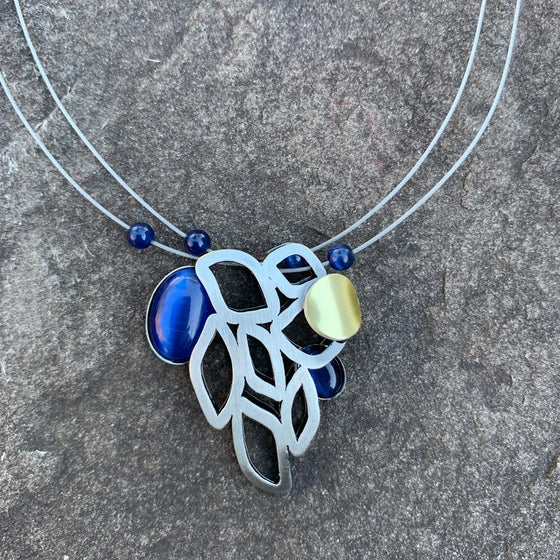 Abstract style necklace. Brushed silver colour leaf shapes with a deep blue glass piece on the corner.