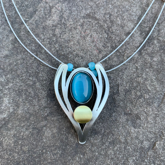 Bold shield shaped necklace. Brushed silver metal surrounding an aqua coloured center piece. resembles the head of a bird from head on.