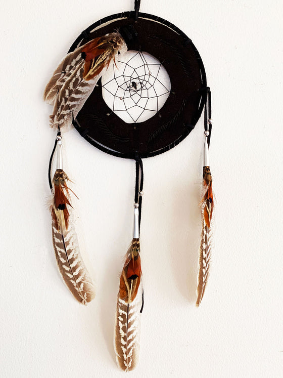 This dream catcher features a ring of brown leather with a hole in the center that is filled with string woven in a spiral pattern. A small brown stone sits in the center. Read, brown, and white feathers lay across the leather ring on the top left, and hang from three leather strings along the bottom.