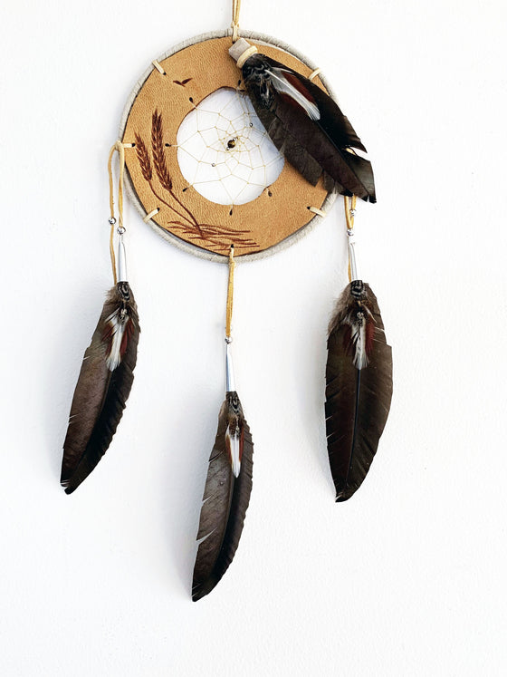 This dream catcher features a ring of tan leather with grain stalks branded onto it. A hole in the center of the leather is filled with string woven in a spiral pattern. A small tan stone sits in the center. White and brown feathers lay across the leather ring on the top right, and hang from three leather strings along the bottom.