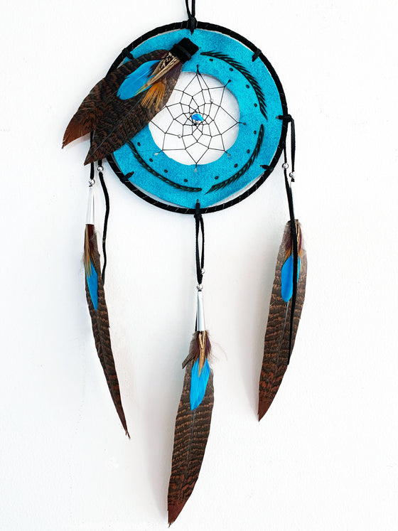 This dream catcher features a ring of teal leather with lines and dots branded onto it. A hole in the center of the leather is filled with string woven in a spiral pattern. A small teal stone sits in the center. Teal, and brown speckled feathers lay across the leather ring on the top left, and hang from three leather strings along the bottom.