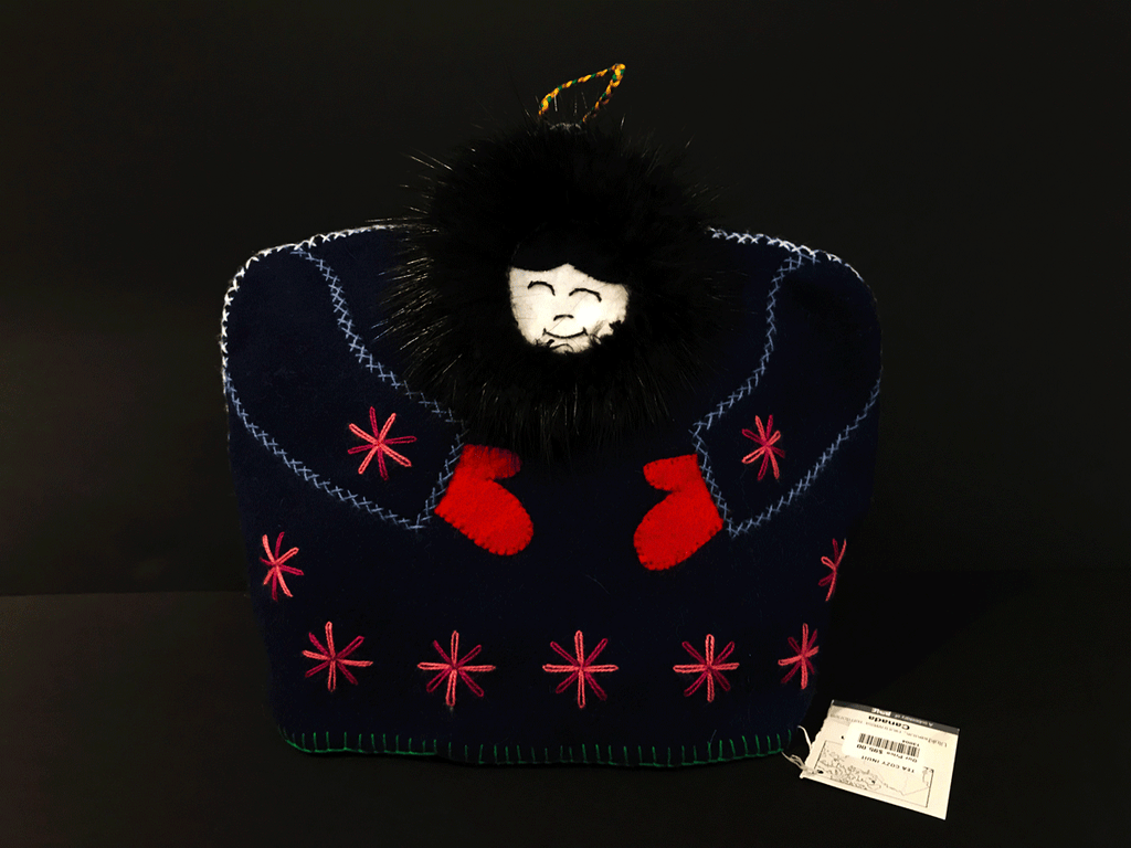 This tea cozy is in the shape of a smiling person wears a navy blue parka with black fur around their face. lightblue stitching outlines the arms, and red mittens poke out from the sleeves. Seven pink stars are stitched along the bottom, and one on each of the sleeves.