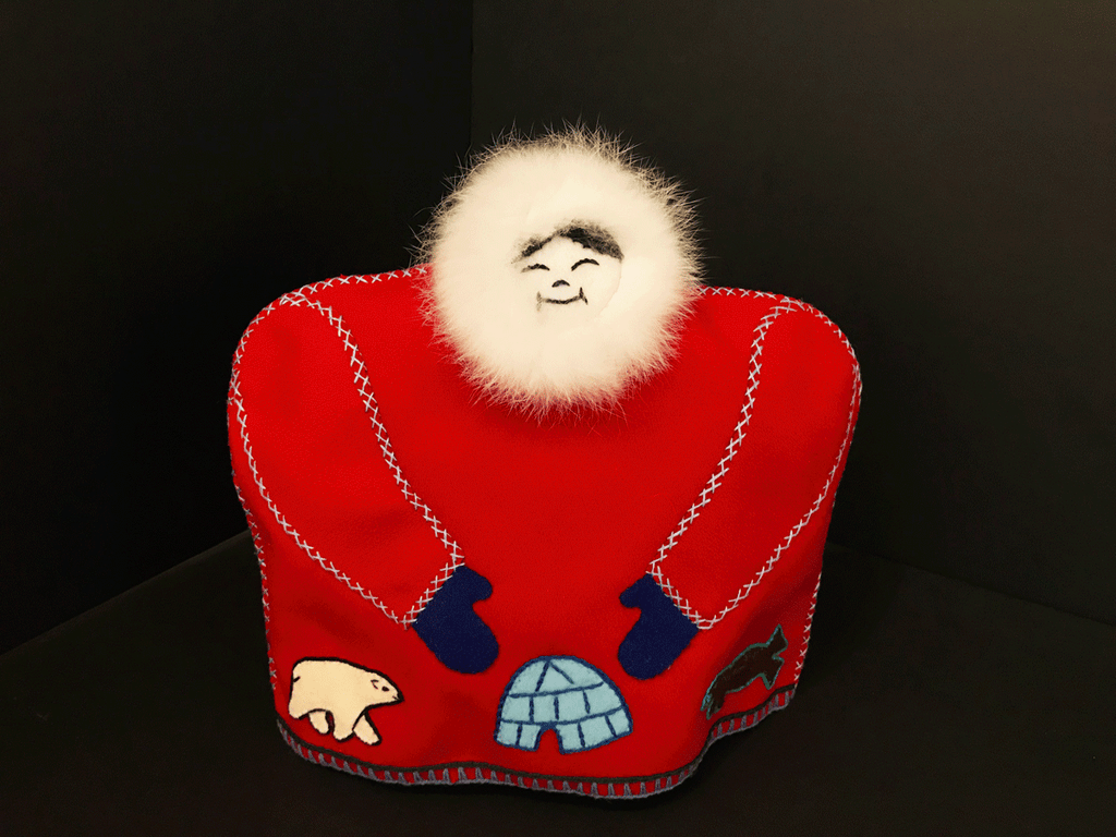 This tea cozy is in the shape of a smiling person wearing a red parka with white fur around their face. White stitching outlines the sleeves, where blue mittens poke out from. A polar bear, an igloo, and a bison are stitched onto the parka along the bottom.