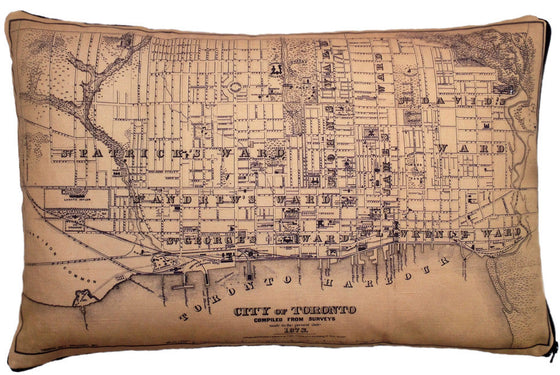 This large pillow features a vintage map of Toronto. The map is printed in black on a tan background. It shows the major wards of the city, the harbor front, and a few prominent landmarks.